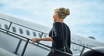 Woman going up aircraft  departing Platinum Service